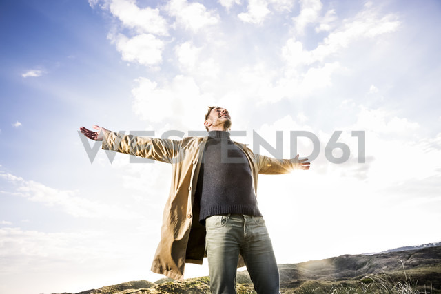 Man standing in dunes with outstretched arms - FMKF04262
