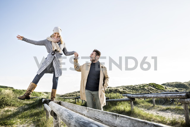 Man helping woman balancing on wooden stakes in dunes - FMKF04265