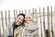 Portrait of smiling couple wrapped in blanket on the beach - FMKF04277