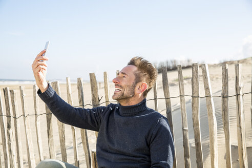 Man taking a selfie at fence on the beach - FMKF04280