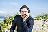 Portrait of man wearing woolly hat on the beach - FMKF04283