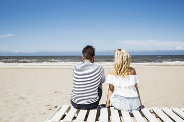 Couple sitting on boardwalk on the beach - FMKF04292