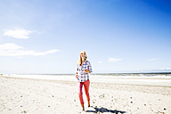 Smiling woman walking on the beach - FMKF04295