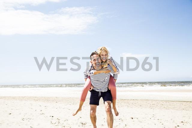 Happy playful couple on the beach - FMKF04301