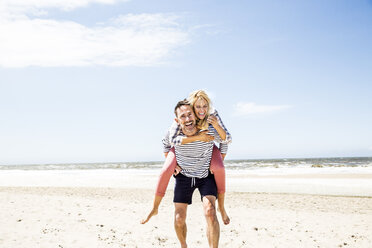 Happy playful couple on the beach - FMKF04301