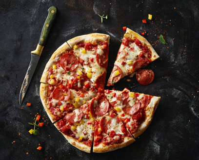 Sliced pizza with salami on dark ground - KSWF01822