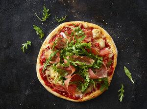 Pizza with ham and rocket on dark ground - KSWF01828