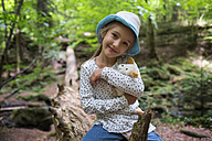 Portrait of smiling little girl with cuddly toy in the woods - DIKF00263