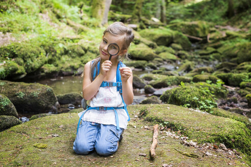 Little girl with magnifier crouching on rock in the woods watching a feather - DIKF00266