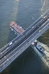 USA, New York City, barge sailing underneath Manhattan Bridge on East River, aerial view - BCDF00280