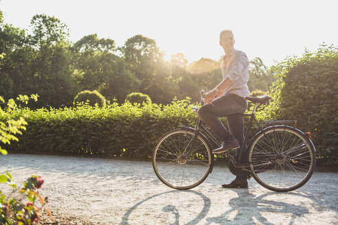 Man with bicycle in a park at sunrise - DIGF02558