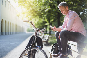 Smiling man with bicycle checking the phone on a park bench - DIGF02570