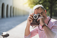 Man taking pictures with an old-fashioned camera in a park - DIGF02573