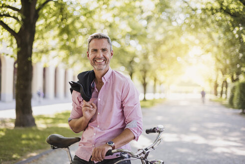 Portrait of smiling man with bicycle in a park - DIGF02576