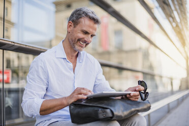 Smiling man sitting in the city using tablet - DIGF02585