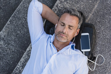 Man with closed eyes lying on stairs with cell phone and earbuds - DIGF02591