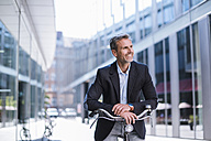 Smiling businessman on bicycle in the city - DIGF02597