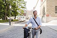 Smiling man pushing bicycle in the city - DIGF02600