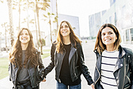 Three happy friends wearing black leather jackets - GIOF02947