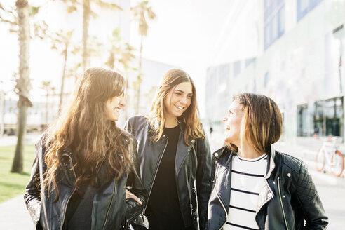 Three friends wearing black leather jackets having fun - GIOF02950