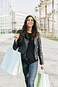 Portrait of smiling woman with shopping bags - GIOF02956