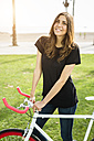 Portrait of smiling young woman with fixie bike - GIOF02959
