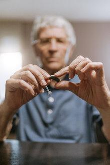 Senior man examining hearing aid - ZEDF00749