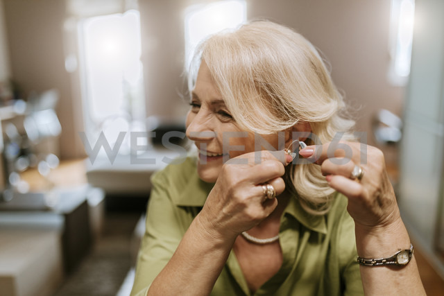 Senior woman applying hearing aid - ZEDF00758