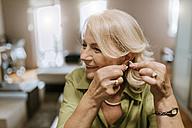 Senior woman applying hearing aid - ZEDF00758