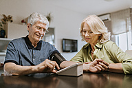 Senior couple taking blood pressure - ZEDF00761