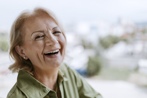 Portrait of laughing senior woman with hearing aid outdoors - ZEDF00767