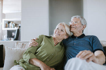 Smiling senior couple sitting on couch at home - ZEDF00773