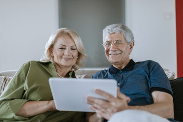 Senior couple at home sitting on couch sharing tablet - ZEDF00776