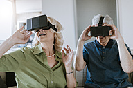 Senior couple at home sitting on couch wearing VR glasses - ZEDF00782
