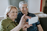 Senior couple at home sitting on couch taking a selfie - ZEDF00785
