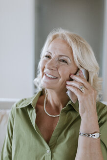 Smiling senior woman at home on cell phone - ZEDF00794