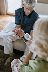 Senior couple taking blood pressure at home - ZEDF00797