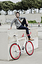 Young man with racing cycle sitting on a wall listening music with headphones - GIOF02976