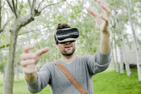 Man wearing virtual reality glasses in nature using his hands - GIOF02979
