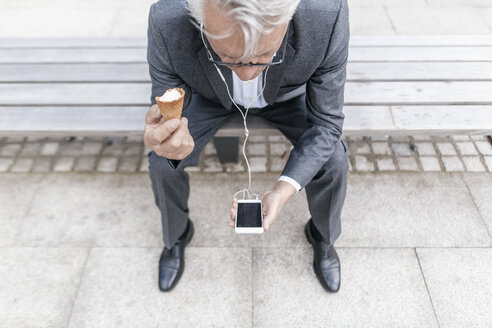 Senior businessman with ice cream cone sitting on bench looking at cell phone - GUSF00049