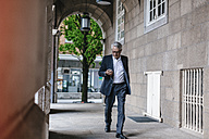 Walking senior businessman with smartphone and earphones - GUSF00052