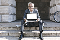 Portrait of senior businessman sitting on stairs showing  laptop - GUSF00058