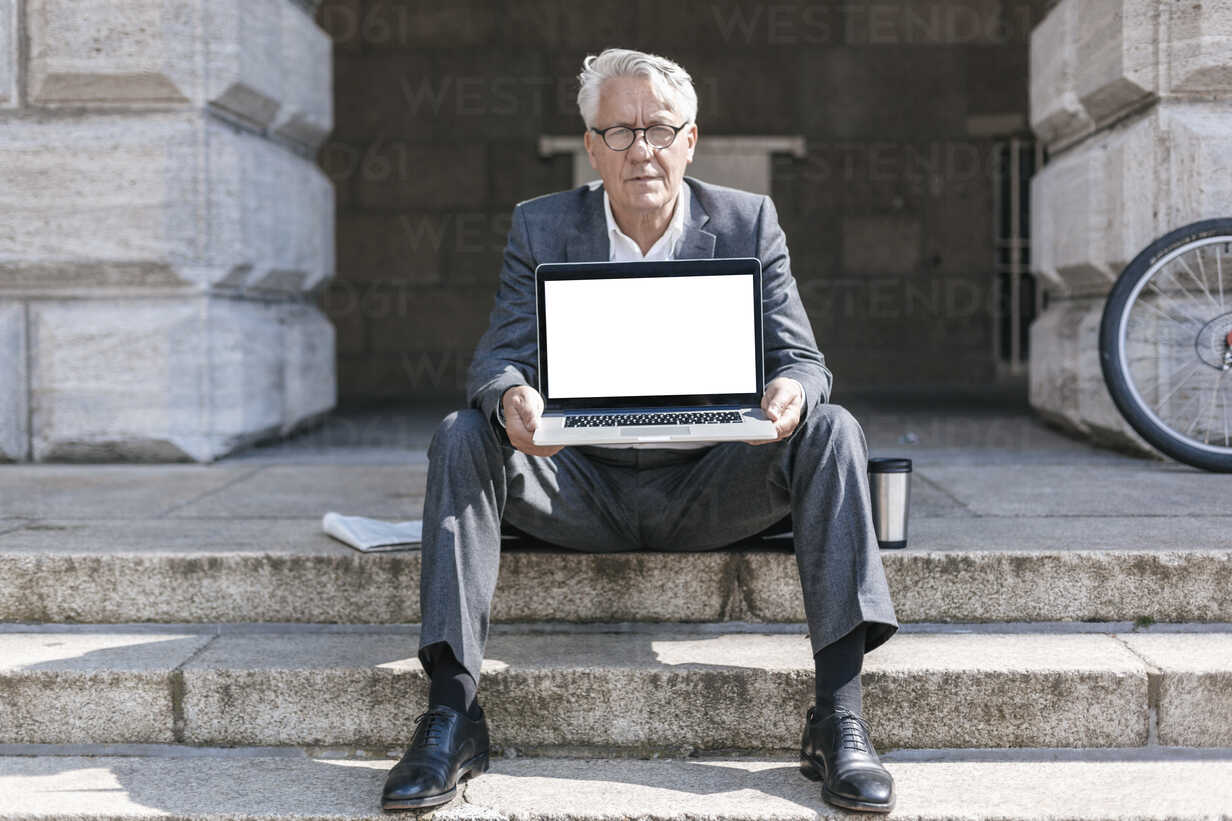 Portrait of senior businessman sitting on stairs showing  laptop - GUSF00058 - Gustafsson/Westend61