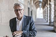 Portrait of senior businessman holding laptop - GUSF00061