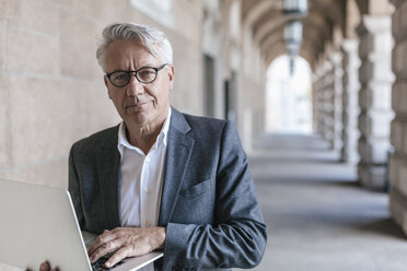 Portrait of senior businessman holding laptop - GUSF00061