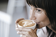 Businesswoman sitting in cafe, drinking coffee - KNSF01860