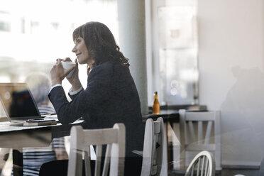 Businesswoamn with laptop, sitting in cafe, drinking coffee - KNSF01887