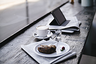 Cake, coffee and tablet pc on a shelf in a cafe - KNSF01890