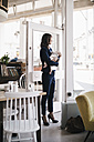 Businesswoman in cafe holding sleeping baby - KNSF01896