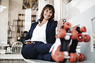 Businesswoman wearing roller skates, holding smartphone - KNSF01899